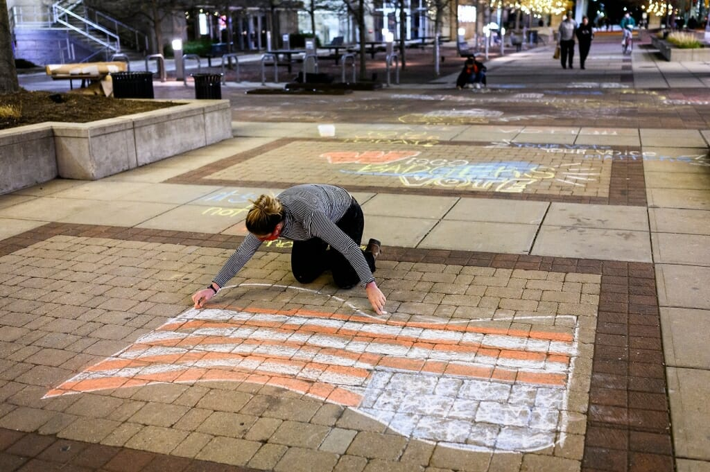 Maloney puts the finishing touches on an American flag, in chalk.