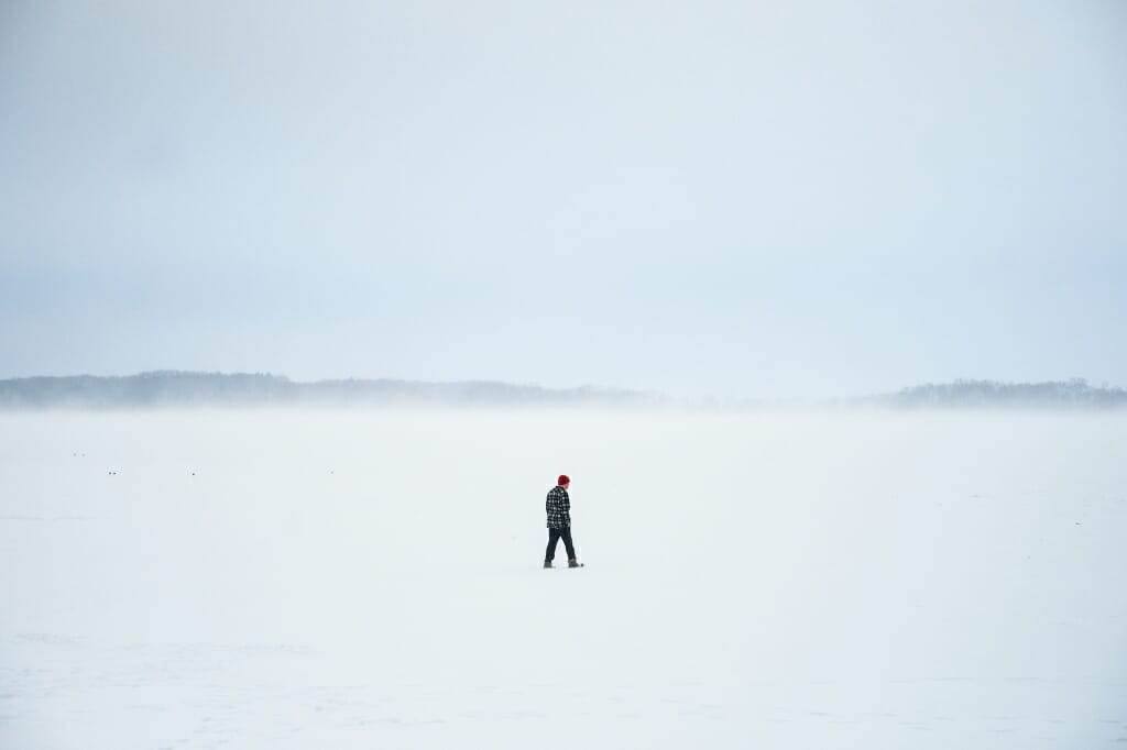 Unidentified person walking on snow-covered lake