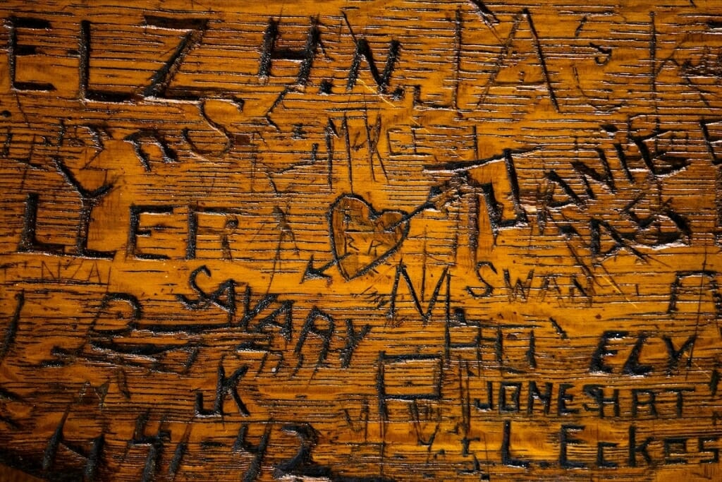 Closeup of tabletop with names carved into wood