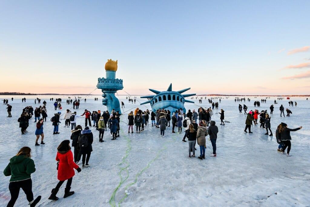 People gathering around Statue of Liberty display on frozen lake