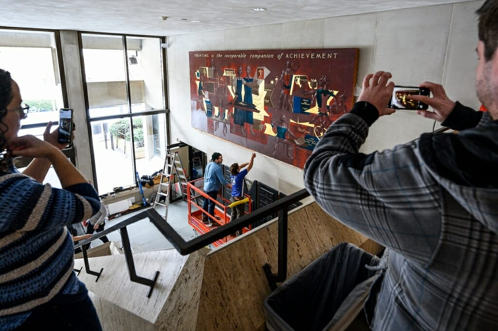 Large picture being installed on a wall
