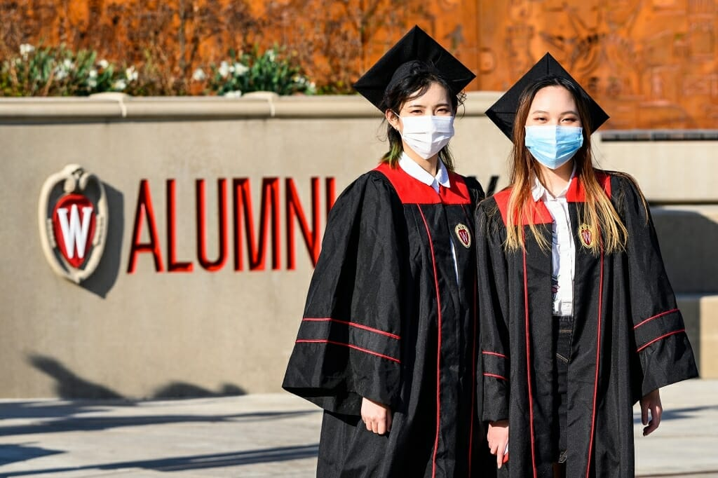 2 people in caps, gowns and face coverings standing in front of the word