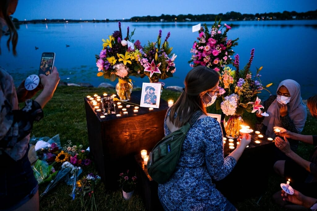 People looking at pictures by candlelight next to lake