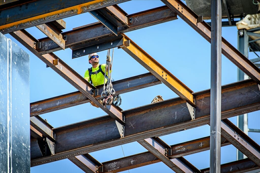 Person working on beams of building under construction