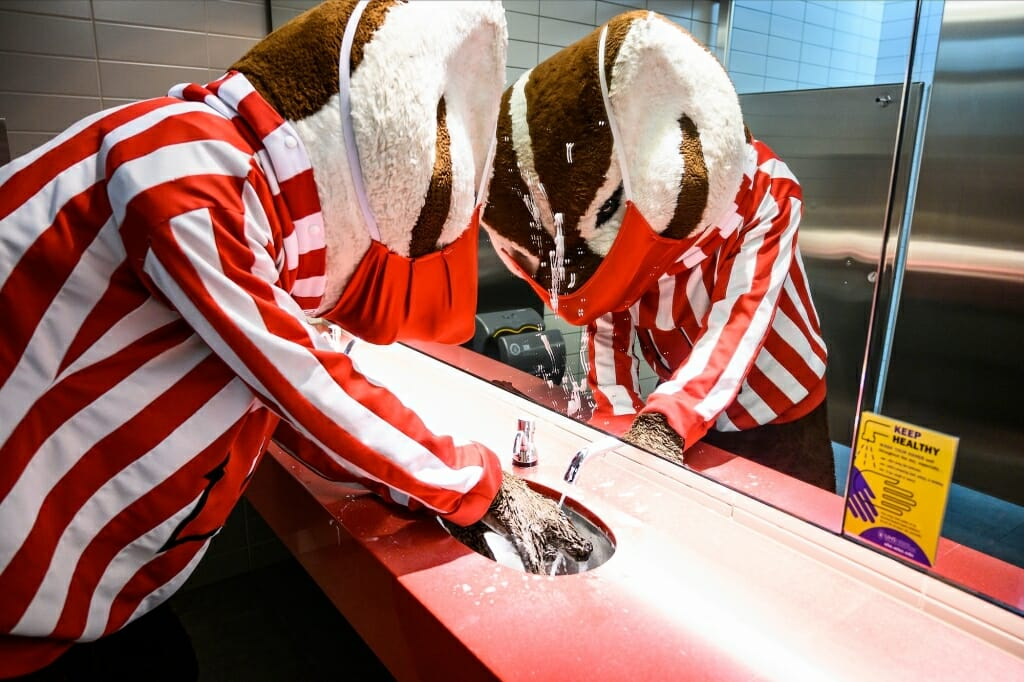 Bucky Badger washing hands at a sink