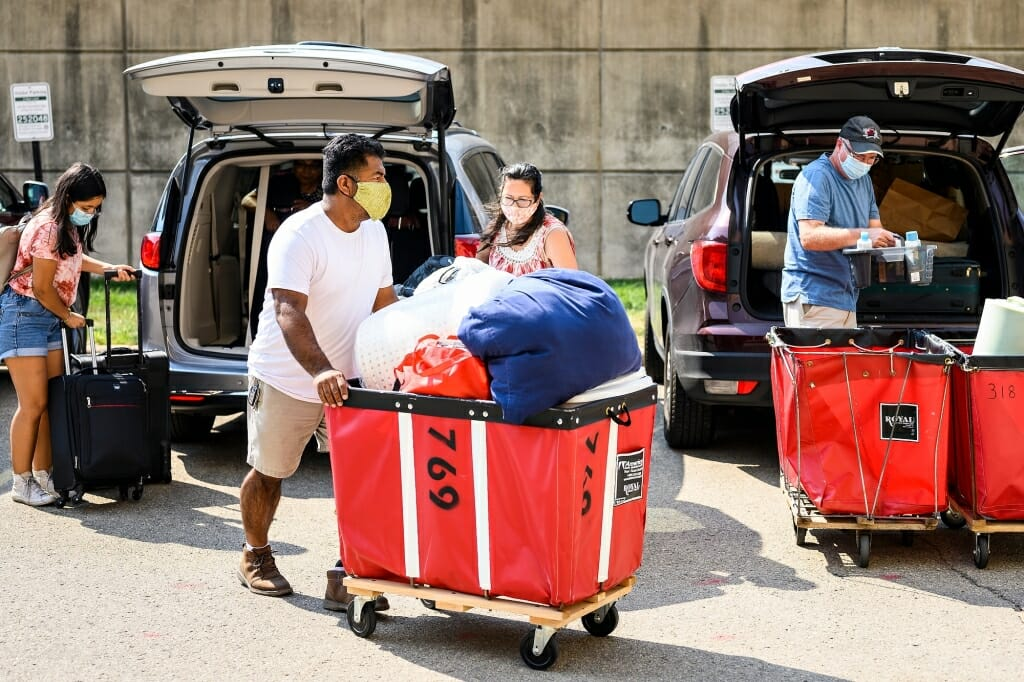 Person pushing laundry cart filled with belongings