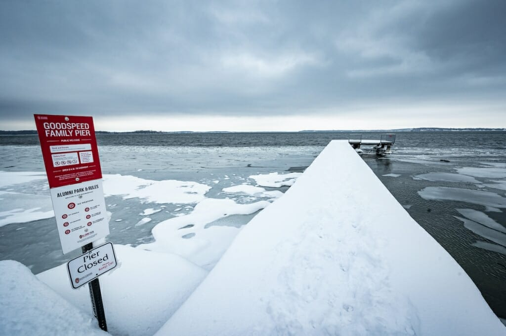 Sign that says Pier Closed next to snow-covered pier