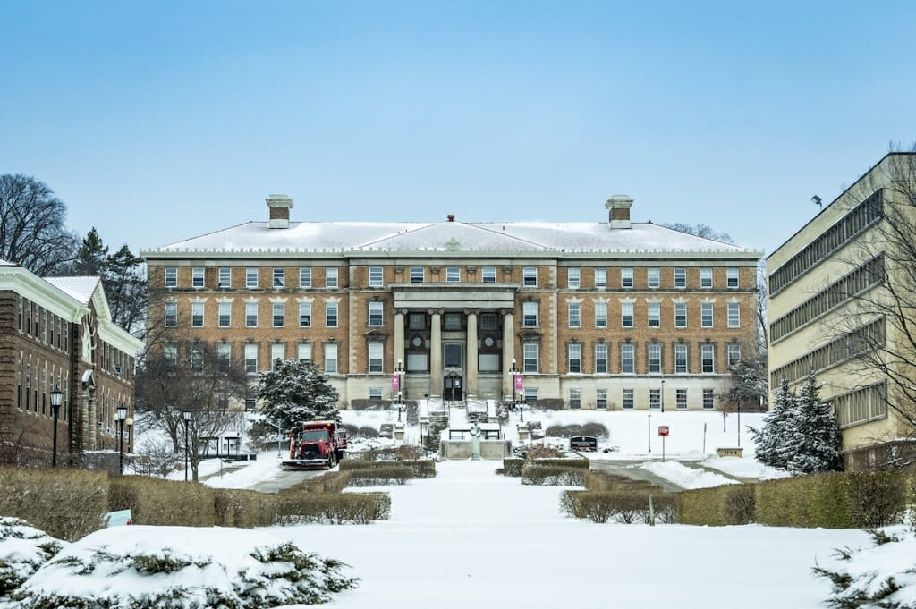 A plow clears snow from Henry Mall in front of Agricultural Hall.