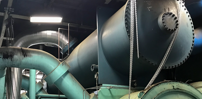 A large tank and pipes form a chiller unit in a power plant
