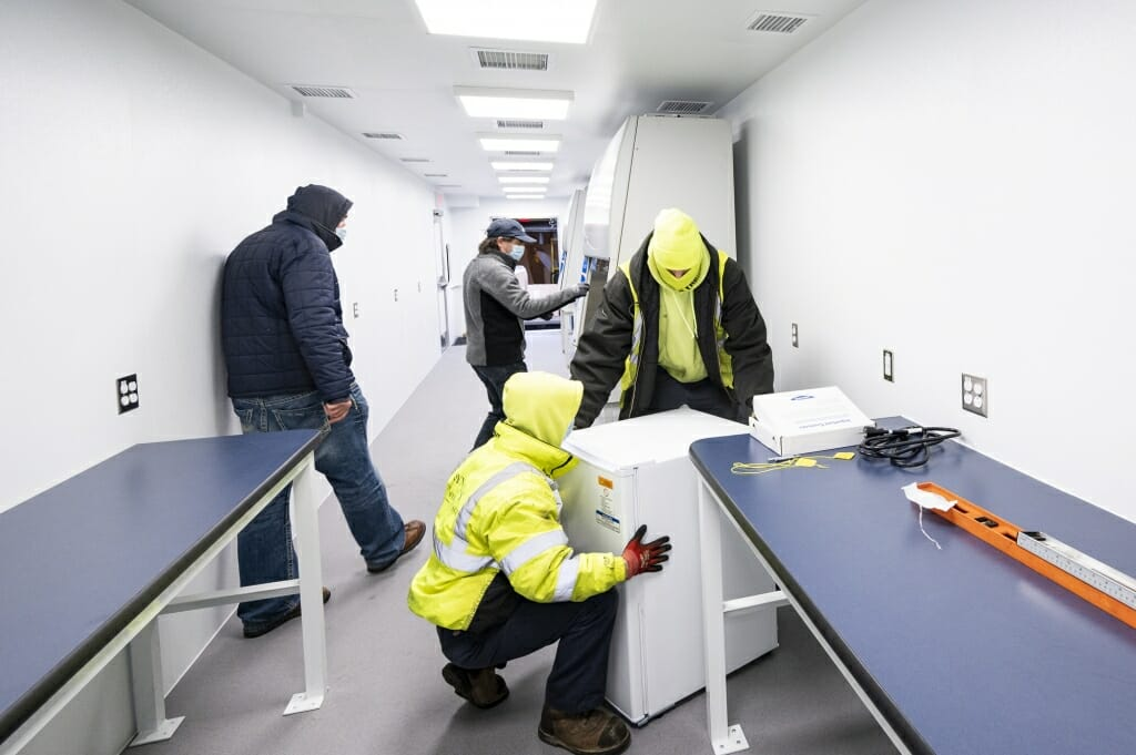 Workers install lab freezers in the mobile testing lab.