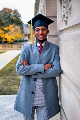 Vershawn Hansen wearing graduation cap and leaning against a building