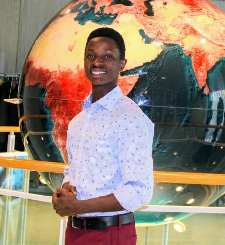 Joel Baraka standing in front of a large globe turned to Africa