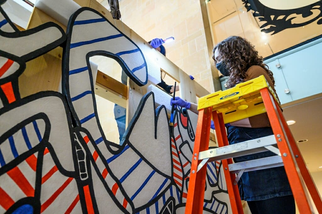 Museum employee Emma Shoer uses an artist's brush to dust the edges of the artwork.