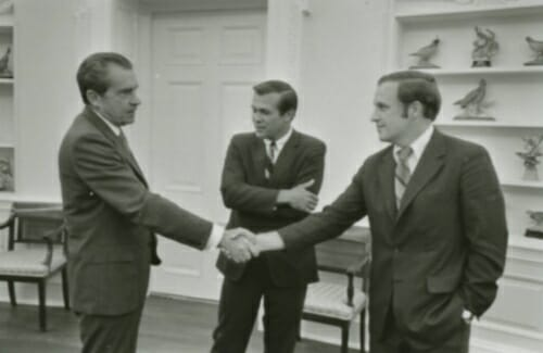 Nixon shaking hands with Cheney as Rumsfeld looks on