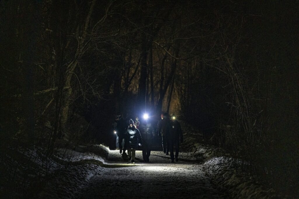 A group of participants wearing headlamps take part in an Outdoor UW night-hike event as they walk down the Howard Temin Lakeshore Path.