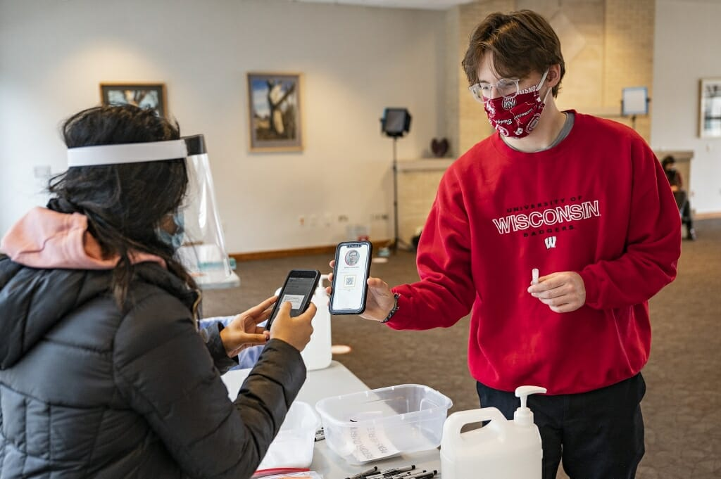Student Sam Kavajecz uses the Safer Badgers phone app when submitting the saliva test. The app QR code is scanned in.