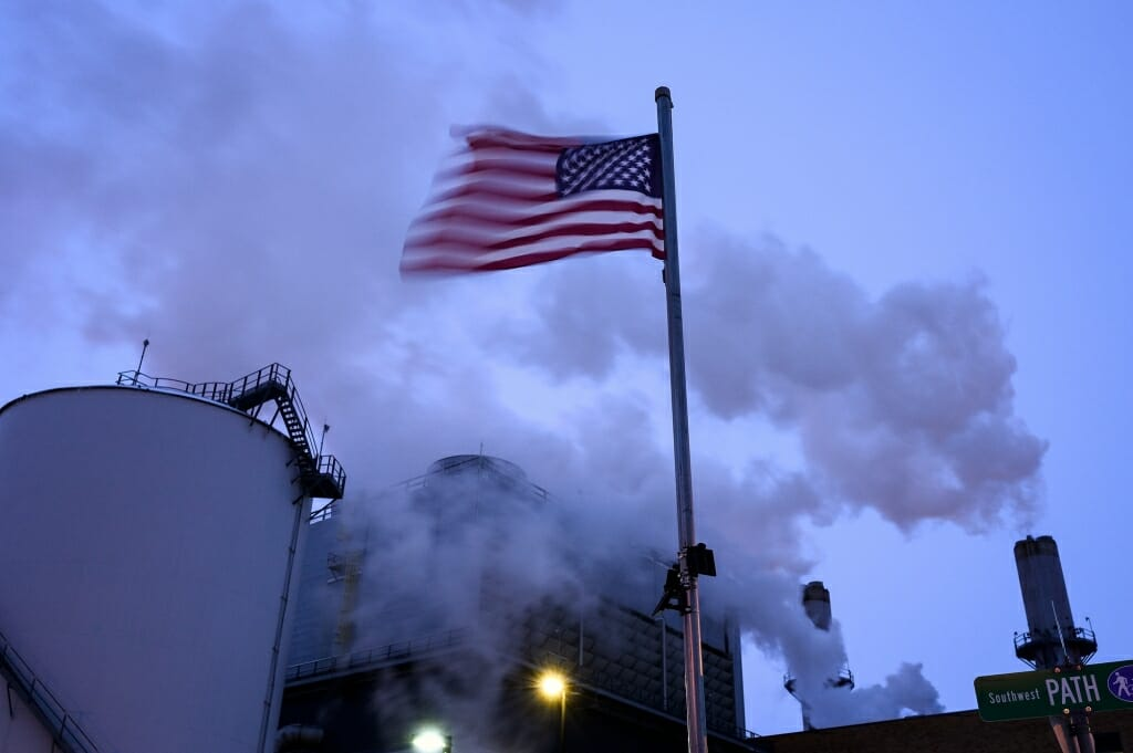 An American flag flutters in the foreground and steam rises from the plant.
