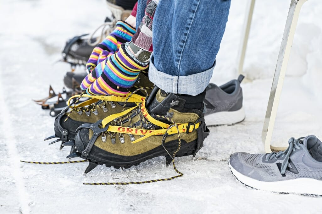 Participants lace up boots with crampons attached to get a good grip on ice.
