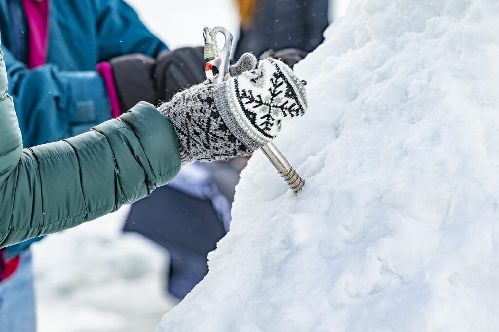 An ice screw is inserted into an ice mound to provide a handhold for climbing.
