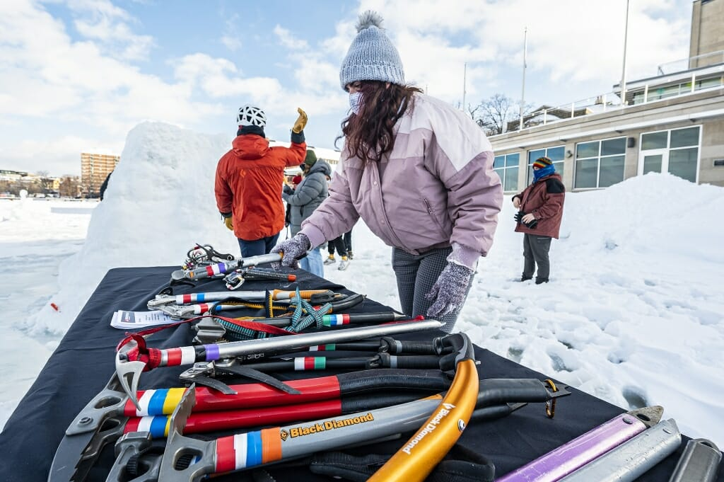 A participant selects an ice axe from a table of climbing equipment.
