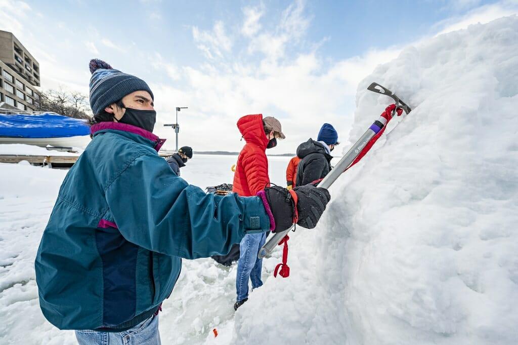 Student Hernan Ballard sinks an ice axe into the ice to get a handhold.