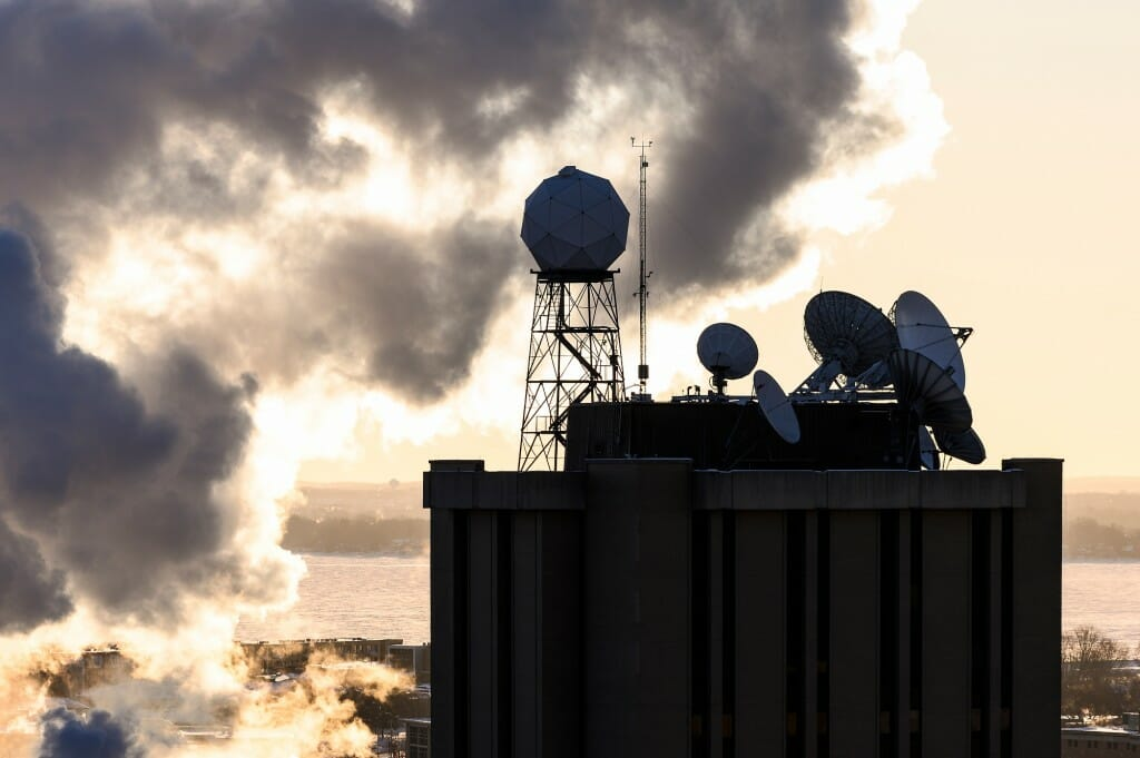 Satellite dishes and meteorological instruments atop the Atmospheric, Oceanic and Space Sciences Building are seen is silhouette during a frigid, subzero winter sunrise on Feb. 7.