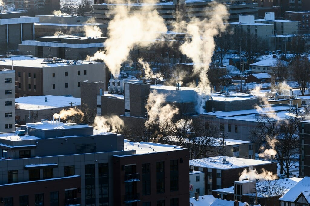 Steam rises from the chimneys and ventilation systems of and snow-covered buildings in the southeast area of campus.