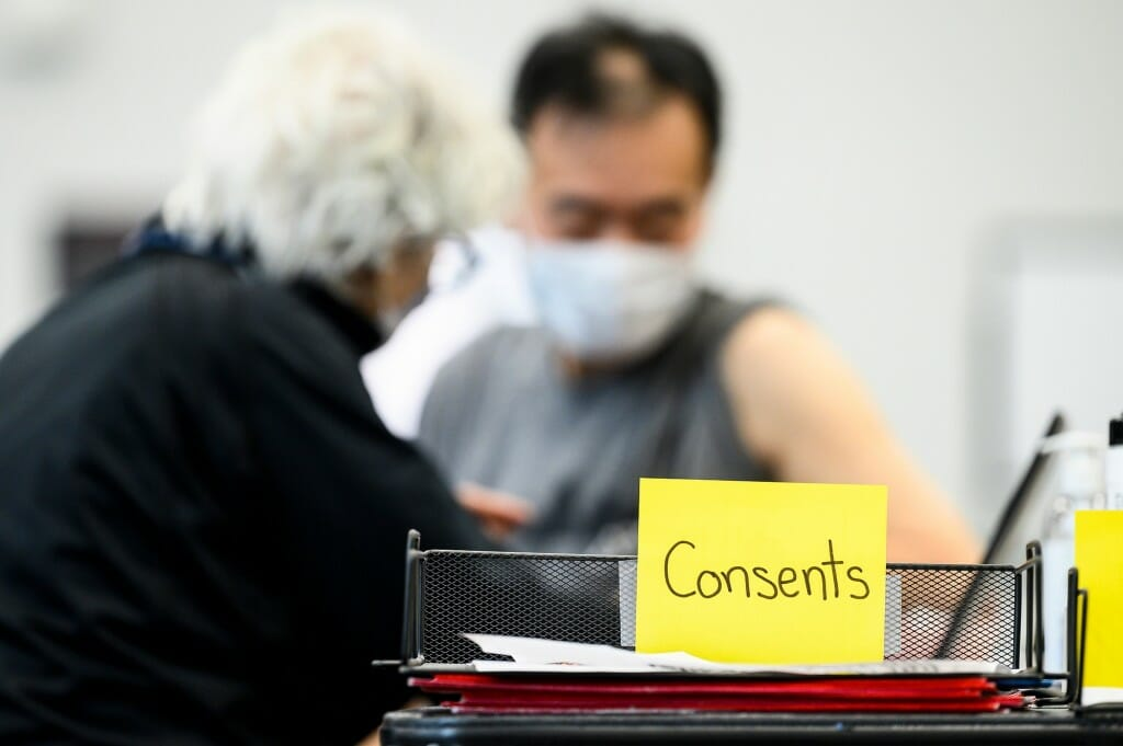 A stack of medical consent forms is pictured as University Health Service nurse practitioner Linda Johnson vaccinates Akihiro Ikeda, a genetics professor.