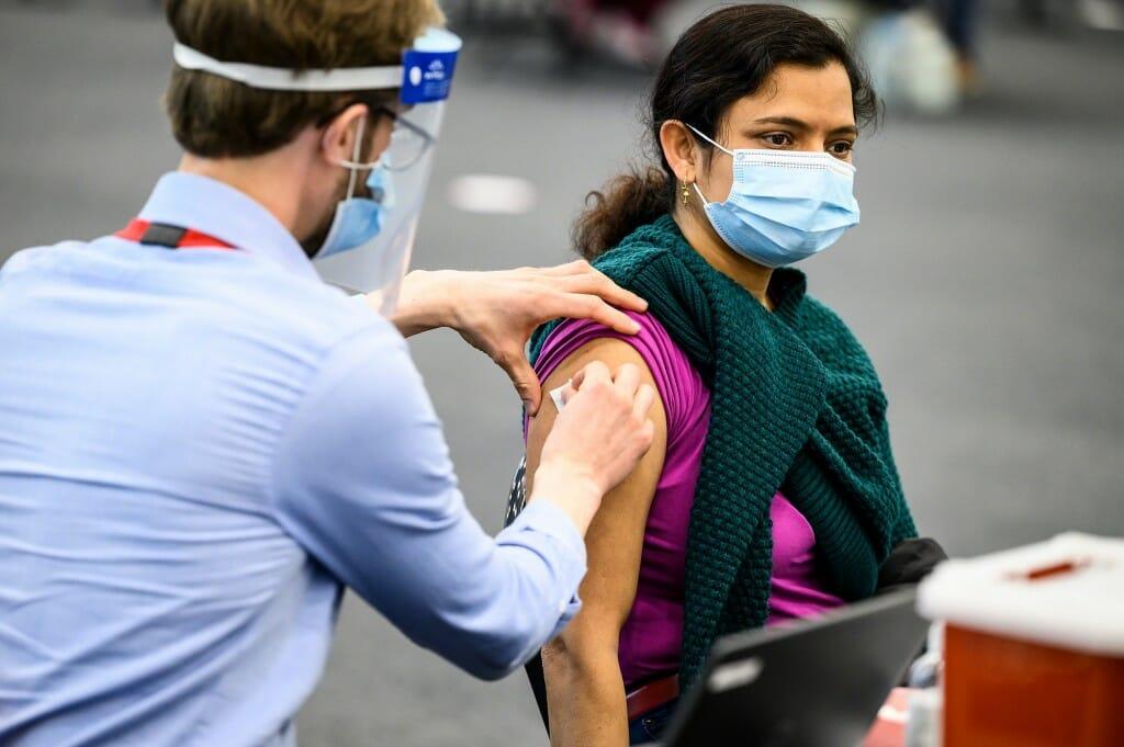 Photo of University Health Service physician assistant Patrick Bohn vaccinating Garima Singh.