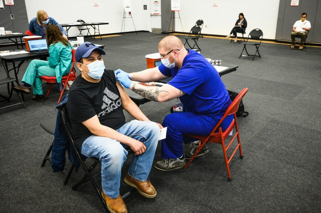 Photo of UHS registered nurse Dan Hunter vaccinating Ricardo Portillo.