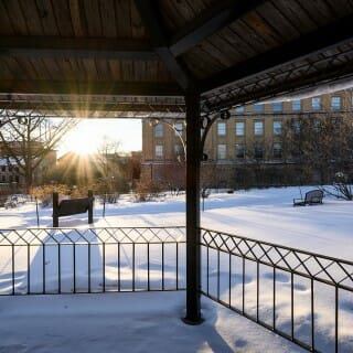 Botany Garden: A silhouetted gazebo frames a view the snow-covered grounds and the setting winter sun.