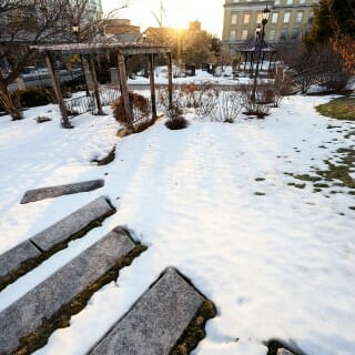 Botany Garden: A series of receding steps is revealed as a snow cover continues to melt and the sun sets on another winter day.