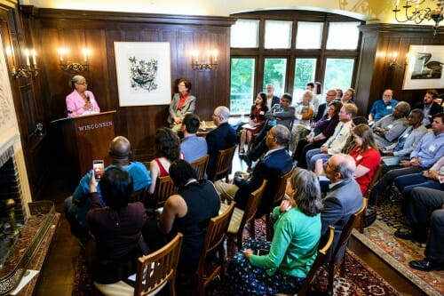 Ladson-Billings standing at podium in wood-paneled room filled with seated spectators