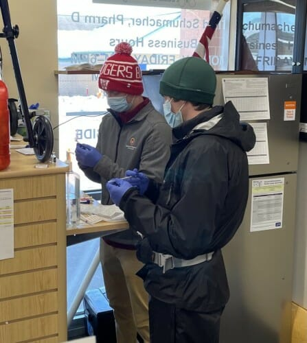 2 people standing at a counter holding syringes
