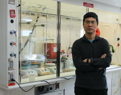 Portrait of Tang posing in his lab