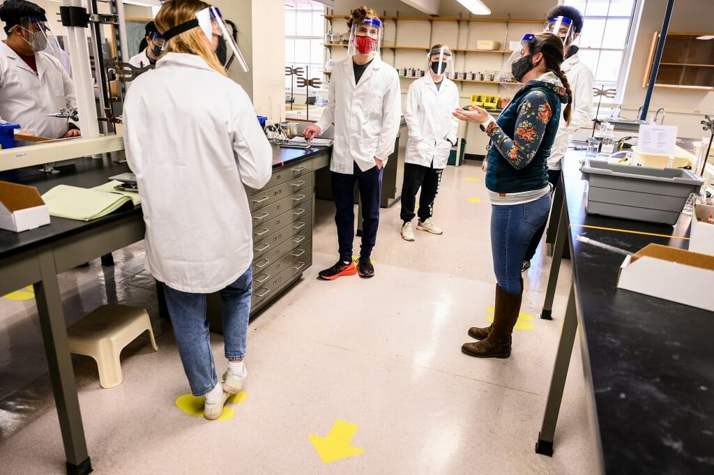 At right, Amanda Buchberger, an assistant faculty associate, checks in with undergraduate students conducting experiments in Chemistry 329: Fundamentals of Analytical Science, taught in the Medical Sciences Center on March 1. The class is one of the largest in-person labs being taught during the Spring 2021 semester.