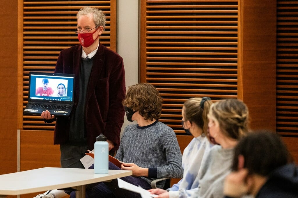 Professor Harry Brighouse holds a laptop displaying two virtual participants as students hold a discussion for Philosophy 304: Topics in Philosophy at the Discovery Building on March 16.