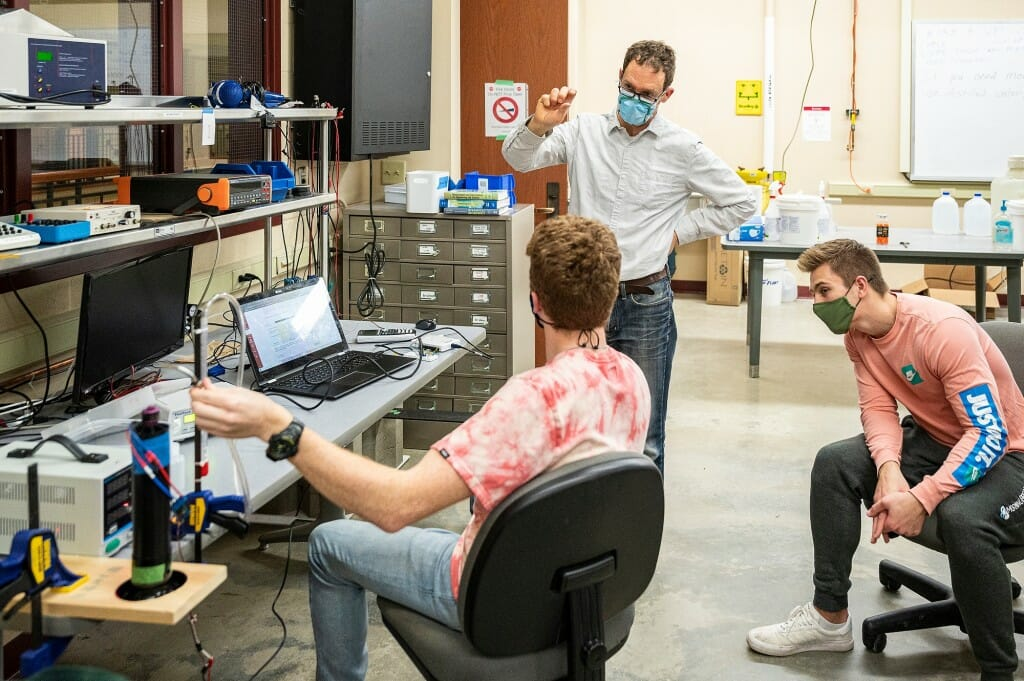 Professor Scott Sanders, standing, discusses a lab project with students Anthony Krotiak (back to camera) and Ben Krimpelbein during Mechanical Engineering 368: Engineering Measurements and Instrumentation, an in-person class and lab taught at the Mechanical Engineering Building on March 8.