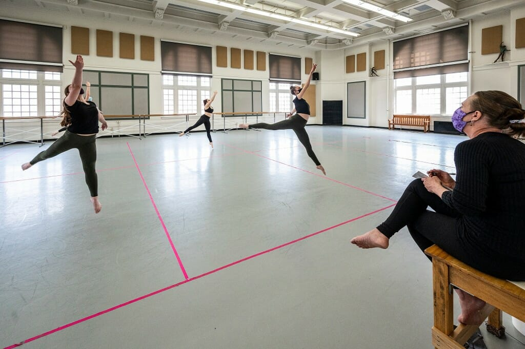 Students perform within their designated 10-feet by 12-feet rehearsal sections during Dance 112: Contemporary Dance Technique and Theory II. The in-person class is taught by faculty associate Karen McShane-Hellenbrand, seated at right, in Lathrop Hall on April 23.