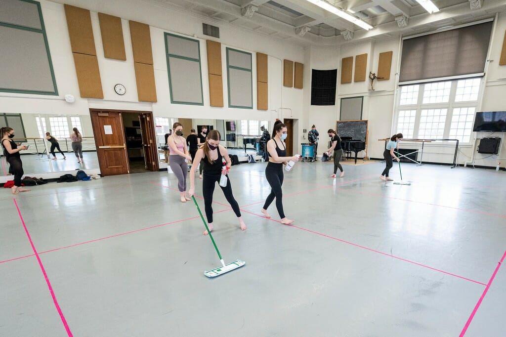 Students clean and sanitize their rehearsal sections  at the end of Dance 112.