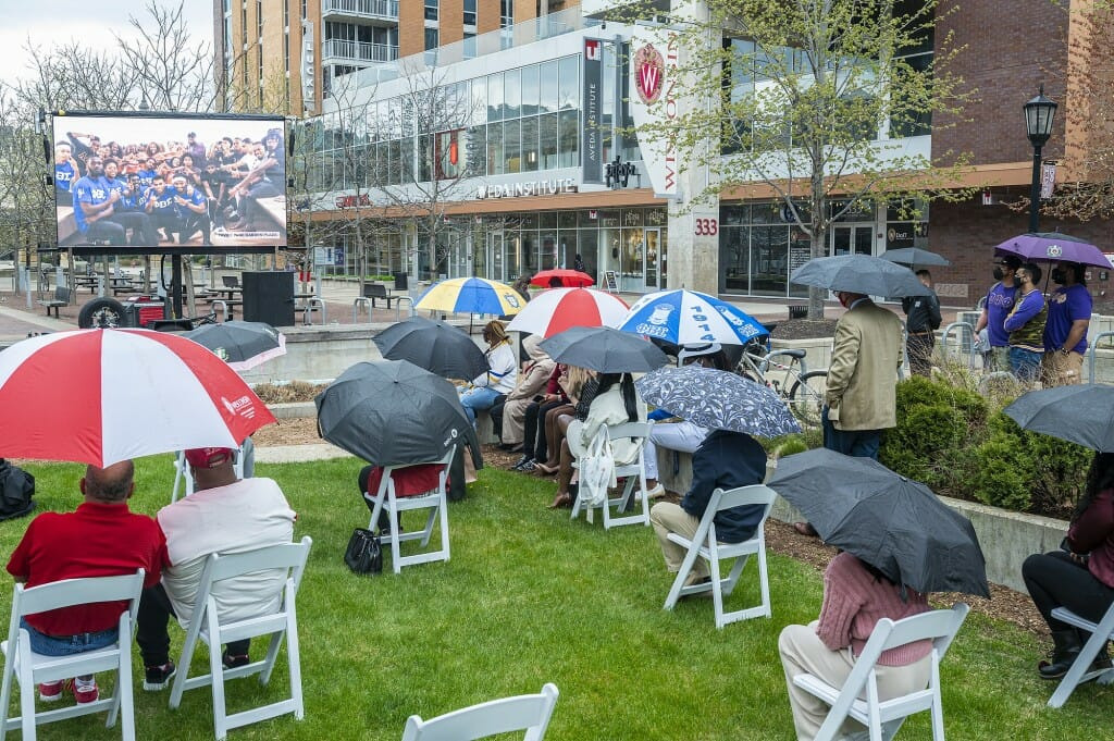 Attendees watch a video presentation on a large outdoor screen during the dedication ceremony.