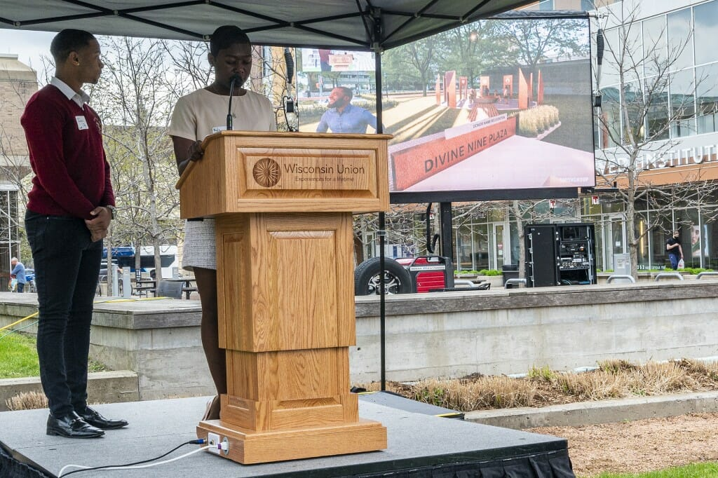 Undergraduates Nyla Mathis (right) and Israel Oby (left) unveil design plans on a large outdoor screen.