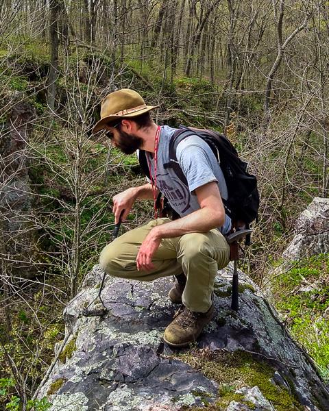 Eric Stewart crouching on a large rock