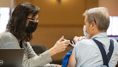 Kim Bertagnoli, vaccinator at UHS, gives Stuart Johnson (right), custodian, his COVID-19 vaccine.