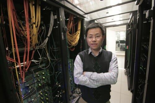 Yu posing between computer racks
