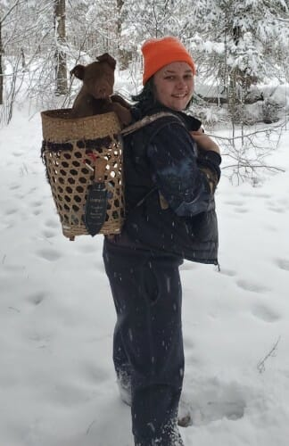 Abi Fergus standing in the snow with a dog in a basket on her back