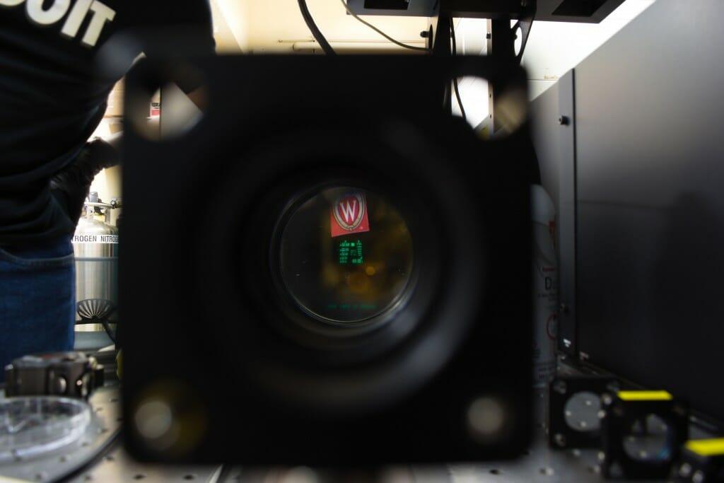 UW crest and green figures seen through lens