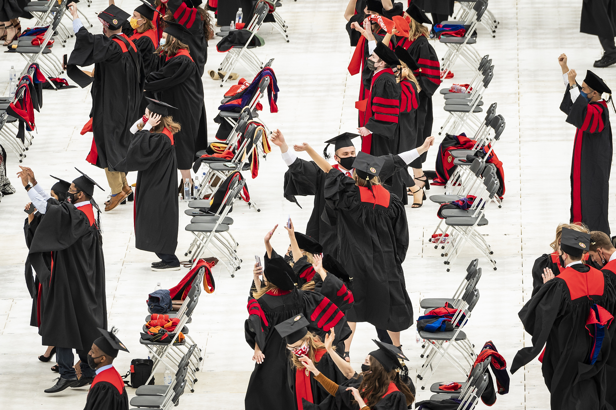 Graduates in caps and gowns hold hands and dance on the field at Camp Randall.