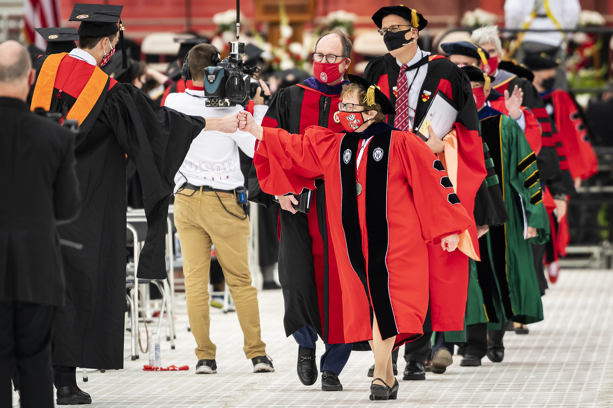 Photo of Chancellor Blank fist bumping a graduate as she leads the commencement procession out of the stadium.