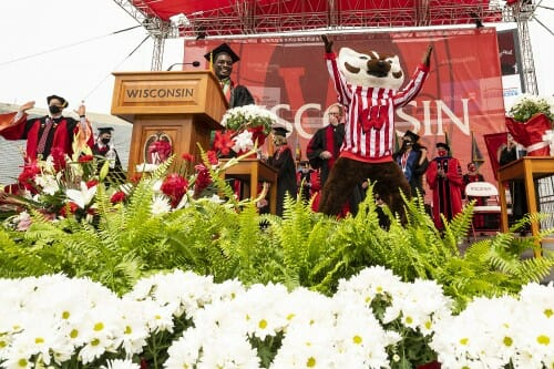 Photo of Mwakatika and Bucky Badger jumping on the stage